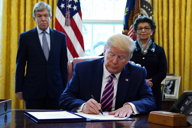 President Donald Trump signs a coronavirus aid package to direct funds to small businesses, hospitals, and testing, in the Oval Office of the White House, Friday, April 24, 2020, in Washington. Sen. Roy Blunt, R-Mo., left, and Jovita Carranza, administrator of the Small Business Administration look on. (AP Photo/Evan Vucci)