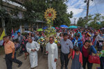 In this Saturday, Oct. 19, 2019, photo, Catholic devotees pull a pedestal with images of the Seven Martyrs at the Christ Church in the Songkhon village, Mukdahan province, northeastern Thailand. There are about 388,000 Catholics in Thailand, representing 0.58 percent of the country's 69 million population. (AP Photo/Sakchai Lalit)
