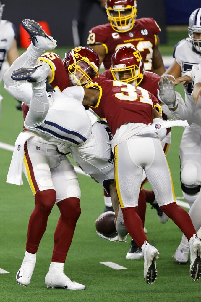 Washington Football Team linebacker Cole Holcomb (55) and safety Kamren Curl (31) upend Dallas Cowboys running back Ezekiel Elliott (21) as he carries the ball in the second half of an NFL football game in Arlington, Texas, Thursday, Nov. 26, 2020. (AP Photo/Ron Jenkins)