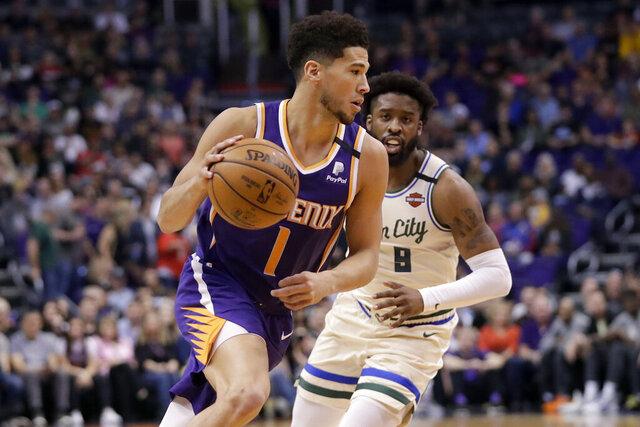 Phoenix Suns guard Devin Booker (1) drives as Milwaukee Bucks guard Wesley Matthews defends during the first half of an NBA basketball game Sunday, March 8, 2020, in Phoenix. (AP Photo/Matt York)