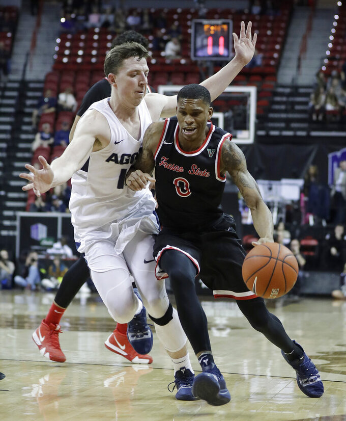 Fresno State's New Williams (0) drives as Utah State's Justin Bean defends during the second half of an NCAA college basketball game in the Mountain West Conference men's tournament Friday, March 15, 2019, in Las Vegas. (AP Photo/Isaac Brekken)