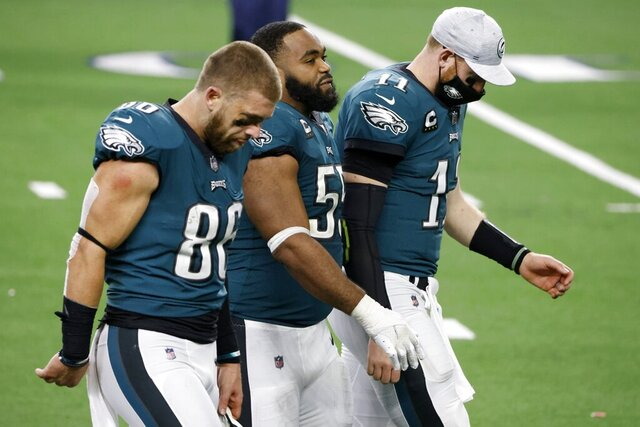 Philadelphia Eagles' Zach Ertz (86), Brandon Graham (55) and Carson Wentz (11), walk off the field after their 37-17 loss to the Dallas Cowboys in an NFL football game in Arlington, Texas, Sunday, Dec. 27. 2020. (AP Photo/Michael Ainsworth)