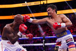 Manny Pacquiao, of the Philippines, hits Yordenis Ugas, of Cuba, in a welterweight championship boxing match Saturday, Aug. 21, 2021, in Las Vegas. (AP Photo/John Locher)