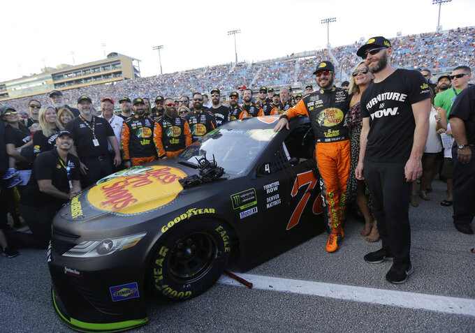 Martin Truex Jr., third from right, poses for a photo with his crew before a NASCAR Series Championship auto race at Homestead-Miami Speedway, Sunday, Nov. 18, 2018, in Homestead, Fla. (AP Photo/Lynne Sladky)