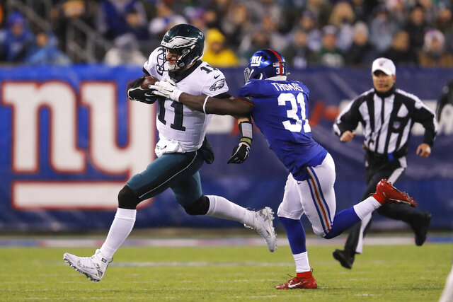 Philadelphia Eagles quarterback Carson Wentz (11) runs with the ball past New York Giants defensive back Michael Thomas (31) in the first half of an NFL football game, Sunday, Dec. 29, 2019, in East Rutherford, N.J. (AP Photo/Adam Hunger)