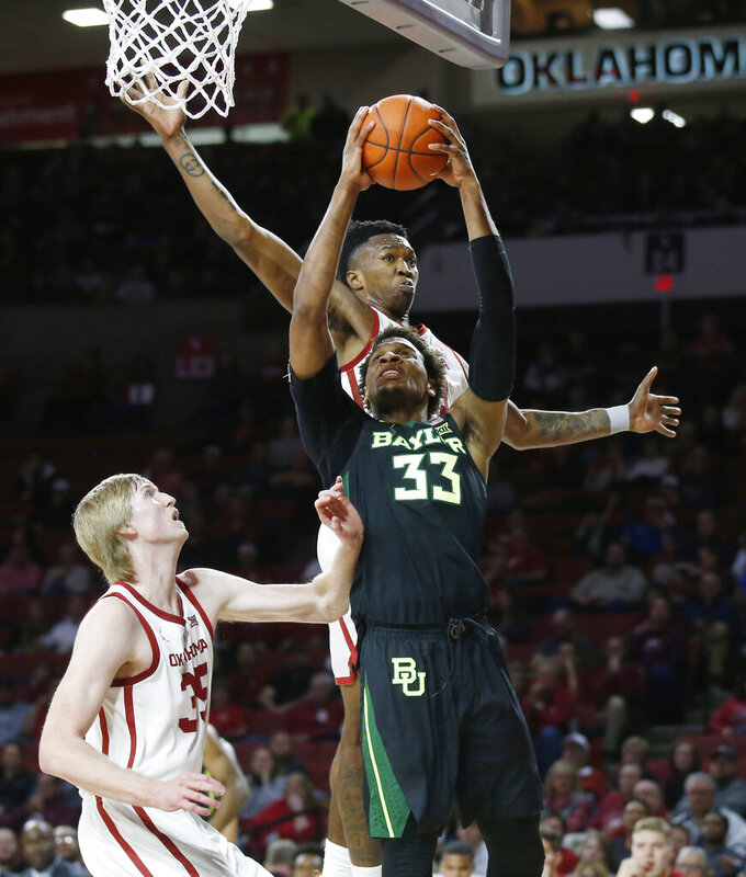 Baylor forward Freddie Gillespie (33) shoots between Oklahoma forward Brady Manek, left, and forward Kristian Doolittle, rear, in the first half of an NCAA college basketball game in Norman, Okla., Monday, Jan. 28, 2019. (AP Photo/Sue Ogrocki)