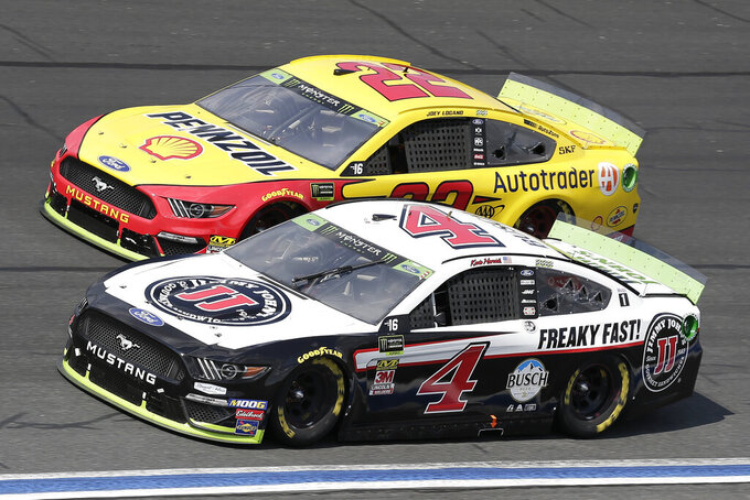 Kevin Harvick (4) and Joey Logano (22) drive through Turn 4 during a NASCAR Cup Series auto race at Charlotte Motor Speedway in Concord, N.C., Sunday, Sept. 29, 2019. (AP Photo/Gerry Broome)