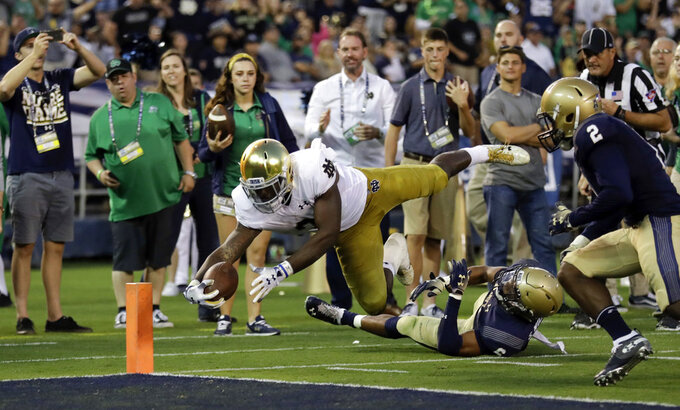 FILE - In this Oct. 27, 2018, file photo, Notre Dame running back Dexter Williams leaps into the end zone for a touchdown during the first half of an NCAA college football game against Navy in San Diego.  Third-ranked Notre Dame will put its unbeaten record on the line when it faces No. 12 Syracuse at New York's Yankee Stadium on Saturday.  (AP Photo/Gregory Bull)