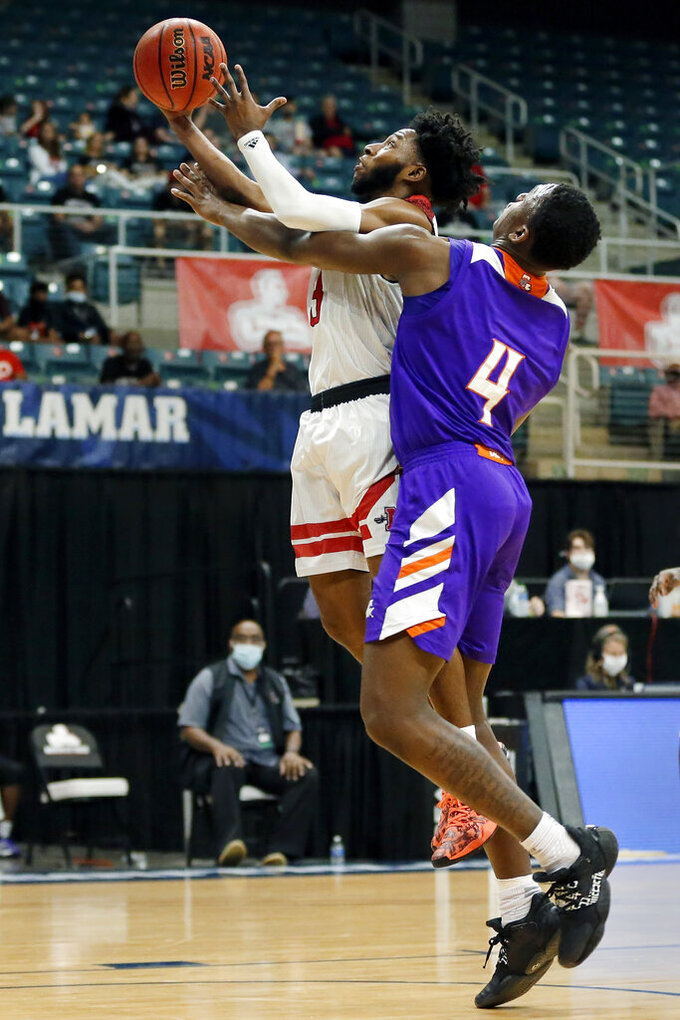Nicholls State guard Kevin Johnson, left, shoots next to Northwestern State center Kendal Coleman (4) during the first half of an NCAA college basketball game in the Southland Conference men's tournament semifinals Friday, March 12, 2021, in Katy, Texas. (AP Photo/Michael Wyke)