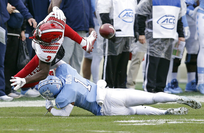 North Carolina State's Kelvin Harmon (3) misses a pass while North Carolina's Myles Dorn (1) defends during the first half of an NCAA college football game in Chapel Hill, N.C., Saturday, Nov. 24, 2018. (AP Photo/Gerry Broome)