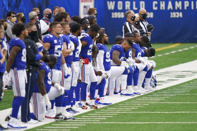 Some of the New York Giants players take a knee during the playing of the national anthem before an NFL football game against the Washington Football Team, Sunday, Oct. 18, 2020, in East Rutherford, N.J. (AP Photo/John Minchillo)