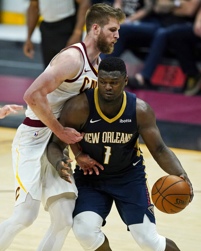 New Orleans Pelicans' Zion Williamson, right, drives to the basket against Cleveland Cavaliers' Dean Wade in the second half of an NBA basketball game, Sunday, April 11, 2021, in Cleveland. (AP Photo/Tony Dejak)