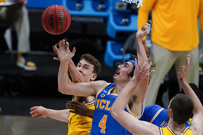 UCLA guard Jaime Jaquez Jr. (4) fights for a rebound with Michigan guard Franz Wagner, left, and center Hunter Dickinson, right, during the first half of an Elite 8 game in the NCAA men's college basketball tournament at Lucas Oil Stadium, Tuesday, March 30, 2021, in Indianapolis. (AP Photo/Michael Conroy)