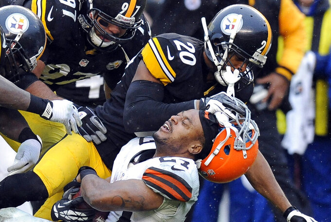 FILE  - In this Dec. 29, 2013, file photo, Cleveland Browns running back Edwin Baker (27) loses his helmet as he is tackled by Pittsburgh Steelers strong safety Will Allen (20) in the third quarter of an NFL football game in Pittsburgh. The Steelers won 20-7. Whether playing in Three Rivers Stadium or at Heinz Field, most of Cleveland's trips down the Turnpike and across the Pennsylvania state line have not gone well. The Browns are just 6-41 on their visits to the Steel City since 1970. (AP Photo/Don Wright, File)