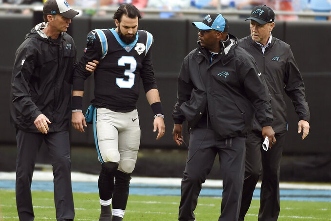 Carolina Panthers quarterback Will Grier (3) walks off of the field as coach Perry Fewell looks on at right during the first half of an NFL football game against the New Orleans Saints in Charlotte, N.C., Sunday, Dec. 29, 2019. (AP Photo/Mike McCarn)