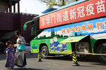 A woman and child wearing period costumes pass by a bus providing COVID-19 vaccination outside the Forbidden City in Beijing on April 14, 2021. If China is to meet its tentative goal of vaccinating 80% of its population against the coronavirus by the end of the year, tens of millions of children may have to start rolling up their sleeves. (AP Photo/Ng Han Guan)