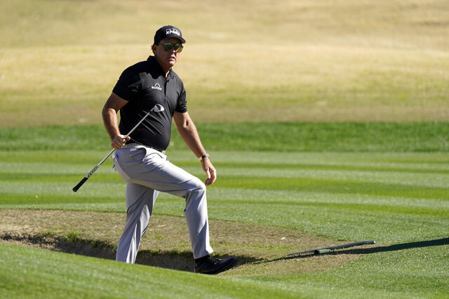 Phil Mickelson walks out from a bunker after hitting to the 17th green during the first round of The American Express golf tournament on the Nicklaus Tournament Course at PGA West Thursday, Jan. 21, 2021, in La Quinta, Calif. (AP Photo/Marcio Jose Sanchez)