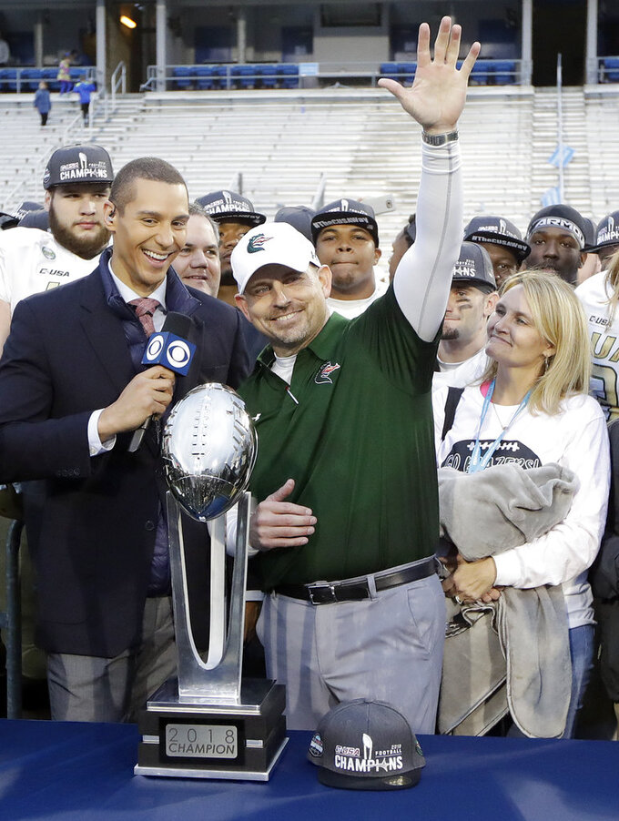 UAB head coach Bill Clark waves as he is presented with the winning trophy after UAB defeated Middle Tennessee in the NCAA Conference USA championship college football game Saturday, Dec. 1, 2018, in Murfreesboro, Tenn. UAB won 27-25. (AP Photo/Mark Humphrey)