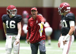 FILE - In this Saturday, April 14, 2018 file photo, Alabama quarterbacks coach Dan Enos talks with quarterbacks Kyle Edwards (16) and Mac Jones (10) before the NCAA college football team's indoor scrimmage in Tuscaloosa, Ala. New coach Manny Diaz calls luring Enos from Alabama the most important transfer he landed this offseason. Few teams have been so shackled by poor quarterback play the past couple seasons. If Enos can turn either N'Kosi Perry, Tate Martell or Jarren Williams into an above-average QB, the Hurricanes' first year under former defensive coordinator Diaz could be a memorable one. (Vasha Hunt/The Birmingham News via AP, File)