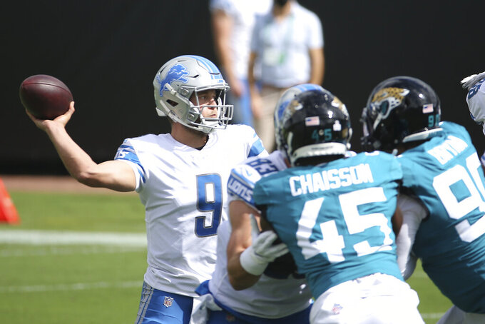 Detroit Lions quarterback Matthew Stafford (9) throws a pass despite pressure from Jacksonville Jaguars linebacker K'Lavon Chaisson (45) and defensive tackle Taven Bryan (90) during the first half of an NFL football game, Sunday, Oct. 18, 2020, in Jacksonville, Fla. (AP Photo/Stephen B. Morton)