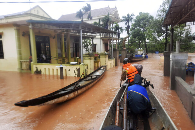 Rescue workers travel by boat to access a flooded village in Quang Tri province, Vietnam, Monday, Oct. 12, 2020. Torrential rains have flooded central Vietnam since last week as the region braces for more heavy rainfall. (Ho Cau/VNA via AP)