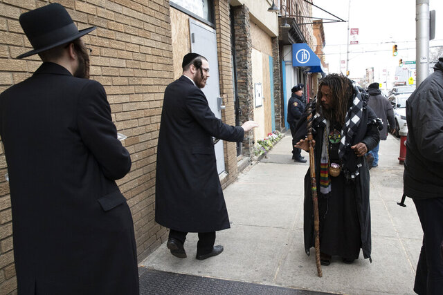 Robert McClain, right, offers condolences to two Jewish men, Friday, Dec. 13, 2019 in Jersey City, N.J. close to the site where three people and two gunmen were shot on Tuesday. New York Mayor Bill de Blasio called the incident a