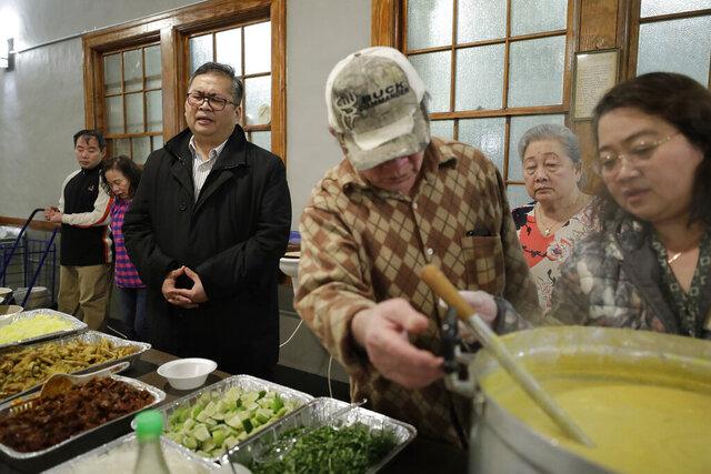 In this Sunday, Feb. 16, 2020, photo Baptist Pastor Clifford Maung, third from left, recites a prayer as Chin Sai, center, and Myint Myint Swe, right, prepare food following services at the Overseas Burmese Christian Fellowship in Boston. All three are immigrants from Myanmar, also known as Burma. Confusion, sorrow and outrage are rippling across some immigrant communities after the announcement of a Trump administration policy that is expected to all but shut down family-based immigration from four countries, including Myanmar. (AP Photo/Steven Senne)