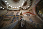 A municipality worker, wearing a protective suit against the coronavirus, disinfects the historical Suleymaniye Mosque, in Istanbul, during the third day of Eid el-Fitr and the last day of a four-day curfew due to the outbreak, Tuesday, May 26, 2020. Istanbul's municipality workers disinfected several mosques which were locked down for more than six weeks and will be partly open again for prayers on Friday, May 29. The Muslim holiday marking the end of the fasting month of Ramadan, traditionally a time of gathering, was marked by a nationwide lockdown to combat the coronavirus. (AP Photo/Emrah Gurel)