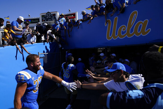 UCLA linebacker Bo Calvert (33) greets fans as he leaves the field after an NCAA college football game against Hawaii Saturday, Aug. 28, 2021, in Pasadena, Calif. UCLA won 44-10. (AP Photo/Ashley Landis)
