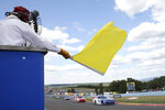FILE - In this Aug. 6, 2016, file photo, a track marshall waves a yellow caution flag during a NASCAR Xfinity series auto race at Watkins Glen International in Watkins Glen, N.Y. As NASCAR speeds back to the race track during the coronavirus pandemic the series has a heavy responsibility to set a safety standard that doesn't slow the return of other sports. (AP Photo/Mel Evans, File)