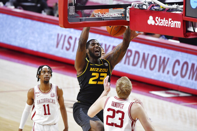 Missouri forward Jeremiah Tilmon (23) dunks the ball over Arkansas defenders Jalen Tate (11) and Connor Vanover (23) during the first half of an NCAA college basketball game in Fayetteville, Ark. Saturday, Jan. 2, 2021. (AP Photo/Michael Woods)