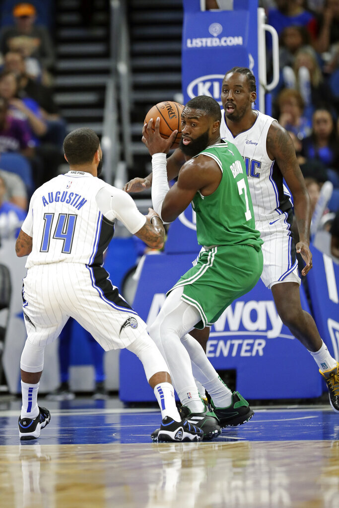 Boston Celtics' Jaylen Brown, center, looks to pass the ball as he is guarded by Orlando Magic's D.J. Augustin (14) and Al-Farouq Aminu , right, during the first half of an NBA preseason basketball game, Friday, Oct. 11, 2019, in Orlando, Fla. (AP Photo/John Raoux)