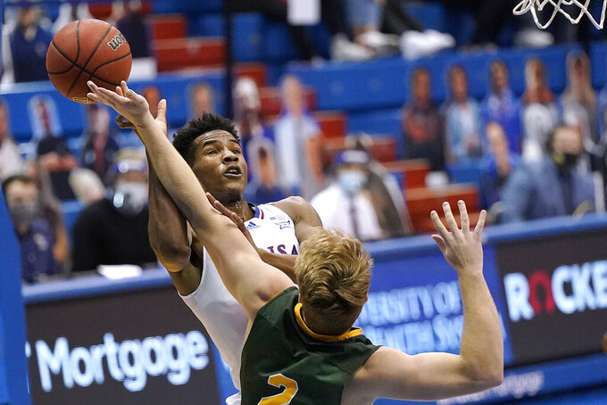 Kansas' Ochai Agbaji, back, shoots under pressure from North Dakota State's Jaxon Knotek (2) during the second half of an NCAA college basketball game Saturday, Dec. 5, 2020, in Lawrence, Kan.  (AP Photo/Charlie Riedel)