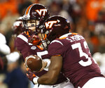 Virginia Tech quarterback Ryan Willis (5) hands the ball off to running back Steven Peoples (32) during the first half of an NCAA college football game against Georgia Tech in Blacksburg, Va., Thursday, Oct. 25, 2018. (AP Photo/Steve Helber)