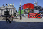 People walk in Piccadilly Circus, in London, Monday, June 14, 2021. British Prime Minister Boris Johnson is expected to confirm Monday that the next planned relaxation of coronavirus restrictions in England will be delayed as a result of the spread of the delta variant first identified in India. (AP Photo/Alberto Pezzali)