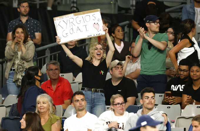 A fans holds a placard in support of Australia's Nick Kyrgios during his third round match against Austria's Dominic Thiem at the Australian Open tennis championship in Melbourne, Australia, Friday, Feb. 12, 2021.(AP Photo/Hamish Blair)