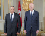 New acting Tunisian Interior Minister Ridha Gharsallaoui , left, and Tunisian President Kais Saiedis poses after a sworn in ceremony at the Presidential Palace in Carthage, outside Tunis, Tunisia, Thursday, July 29, 2021. Tunisian President Kais Saied on Thursday appointed Ridha Gharsallaoui, a former national security adviser to the presidency, to run the Interior Ministry. (Slim Abid/Tunisian Presidency via AP)