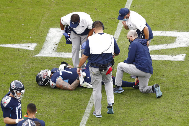 Tennessee Titans offensive tackle Taylor Lewan (77) lies on the ground after being injured in the second half of an NFL football game against the Houston Texans Sunday, Oct. 18, 2020, in Nashville, Tenn. (AP Photo/Wade Payne)