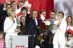 FILE - This Sunday, July 12, 2020 file photo shows Polish President Andrzej Duda flashing a victory sign, joined by with wife Agata Kornhauser-Duda, front left, and daughter Kinga Duda, front right, on the night of his re-election, in Pultusk, Poland. Duda has appointed his 25-year-old daughter as an unpaid adviser on social issues, a move that has triggered accusations of nepotism.(AP Photo/Czarek Sokolowski, File)