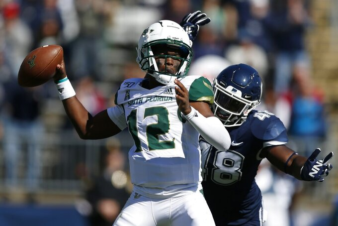 South Florida quarterback Jordan McCloud (12) passes under pressure from Connecticut defensive lineman Kevon Jones (48) during the first half of an NCAA college football game in East Hartford, Conn., Saturday, Oct. 5, 2019. (AP Photo/Michael Dwyer)