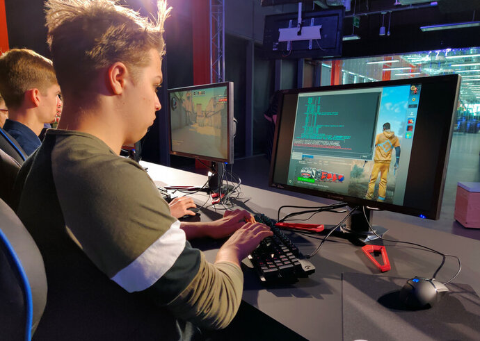 "In this photo taken on Sept. 17, 2019, Ryan Chapman and other students starting Staffordshire University's esports degree course play ""Counter-Strike"" in the school's new London digital studio. A number of U.K. and U.S. universities are launching degrees in esports, or competitive multiplayer videogaming, to capitalize on the booming industry's growing demand for skilled professionals. (AP Photo/Kelvin Chang)"
