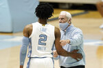 North Carolina head coach Roy Williams speaks with guard Caleb Love (2) during the first half of an NCAA college basketball game against North Carolina State in Chapel Hill, N.C., Saturday, Jan. 23, 2021. (AP Photo/Gerry Broome)