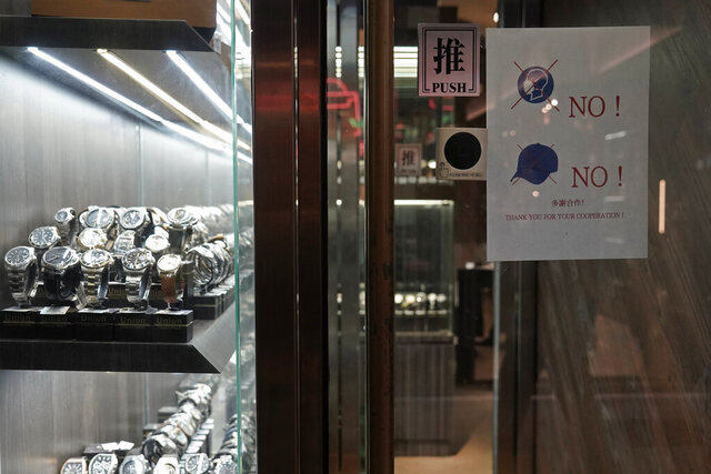 In this Wednesday, Dec. 18, 2019, photo, a notice is attached to the front door demanding no hats and masks allowed in the watch store to help prevent robberies after the shop was attacked by armed robbers recently in Mongkok, a shopping district of Hong Kong. Sellers of luxury goods that are easily peddled by thieves have become targets for armed robbery gangs during the pro-democracy protests that have been gripping Hong Kong. (AP Photo/Kin Cheung)