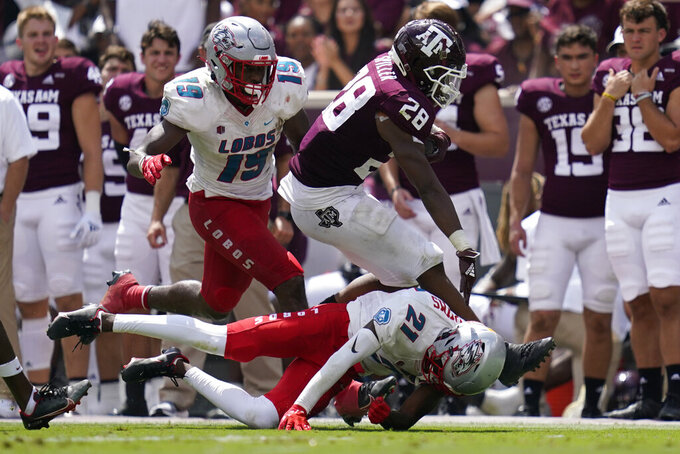 Texas A&M running back Isaiah Spiller (28) is tackled by New Mexico cornerback A.J. Odums (21) after a 47-yard gain during the second half of an NCAA college football game on Saturday, Sept. 18, 2021, in College Station, Texas. (AP Photo/Sam Craft)