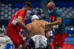 Jacek Zcech, from Poland, is assisted after competing at Men's 100m Backstroke - S2 Heat 1 at the Tokyo Aquatics Centre during the Tokyo 2020 Paralympic Games, Wednesday, Aug. 25, 2021, in Tokyo, Japan. (AP Photo/Emilio Morenatti)