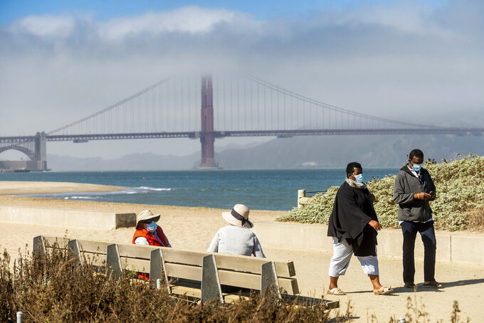 With the Golden Gate Bridge in the background, walkers wear masks while strolling at Crissy Field East Beach in San Francisco on Thursday, Oct. 22, 2020. As the coronavirus pandemic transforms San Francisco's workplace, legions of tech workers have left, able to work remotely from anywhere. Families have fled for roomy suburban homes with backyards. The exodus has pushed rents in the prohibitively expensive city to their lowest in years. (AP Photo/Noah Berger)