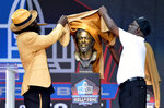 Former NFL player Ed Reed, left, and his presenter, Edward Reed Sr., unveil a bust of Reed during the induction ceremony at the Pro Football Hall of Fame, Saturday, Aug. 3, 2019, in Canton, Ohio. (AP Photo/David Richard)