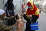 A health worker administers a polio vaccine to a child in Lahore, Pakistan, Monday, March 29, 2021. Despite a steady rise in coronavirus cases, Pakistan on Monday launched a five-day vaccination campaign against polio amid tight security, hoping to eradicate the crippling children's disease this year. (AP Photo/K.M. Chaudary)