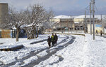 Youths walk on a snow-covered road after a heavy snowfall in Quetta, capital of Pakistan's southwestern Baluchistan province, Monday, Jan. 13, 2020. Severe winter weather has struck parts of Afghanistan and Pakistan, with heavy snowfall, rains and flash floods that left more than 40 dead, officials said Monday as authorities struggled to clear and reopen highways and evacuate people to safer places. (AP Photo/Arshad Butt)