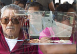 In this May 15, 2019 photo shot through a window, passengers ride a public transit bus through the Iztapalapa borough of Mexico City. Vicious armed robberies have gotten so common aboard buses in Mexico City that commuters have come up with a clever if disheartening solution: Many are buying fake cellphones, to hand over to thieves instead of their real smartphones. (AP Photo/Rebecca Blackwell)